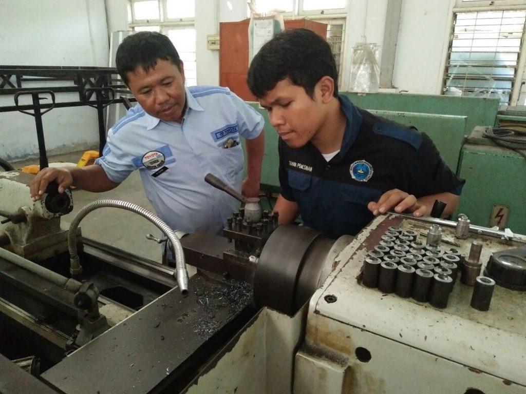 Bpk. Mohamad Rahino, S.Pd sedang membimbing seorang siswa dalam menggunakan Mesin Bubut