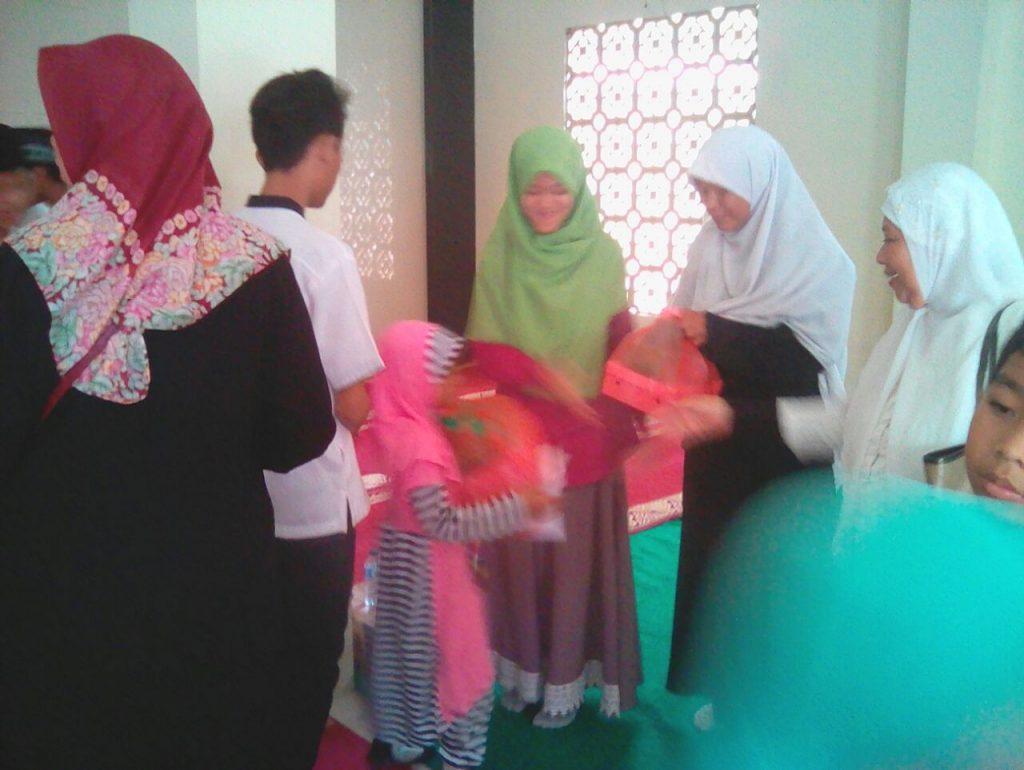 Anggota Rohis SMNK 1 membantu menyalurkan bingkisan kpd anak yatim